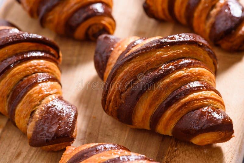 新鲜的自创新月形面包用木表面上的巧克力 免版税库存照片