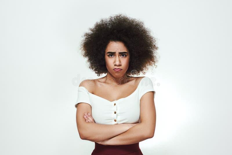 改善不接触我!保持胳膊横渡和做哀伤的面孔的乏味年轻美国黑人的妇女,当站立反对时 库存照片
