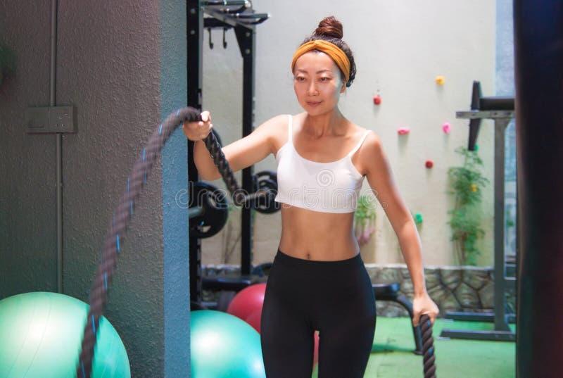 活跃女孩做与健身绳索的锻炼在健身房 免版税库存图片