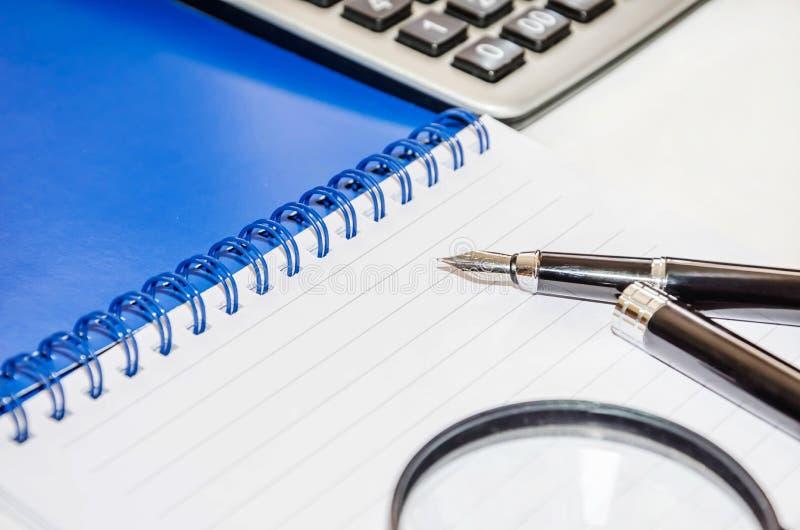 放大器、笔、计算器和笔记本在白色背景 库存照片