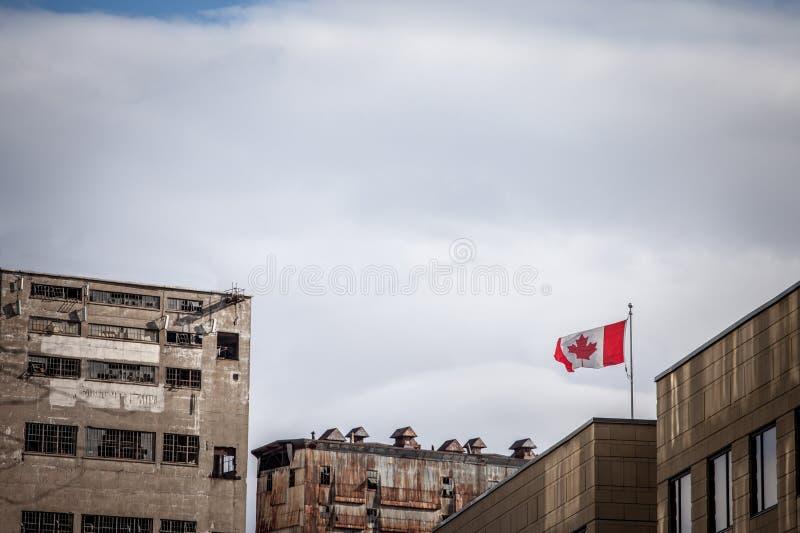 放弃在一个老工业区前面的加拿大旗子由被放弃的筒仓、工厂和仓库做成在蒙特利尔口岸,Quebe 免版税库存图片