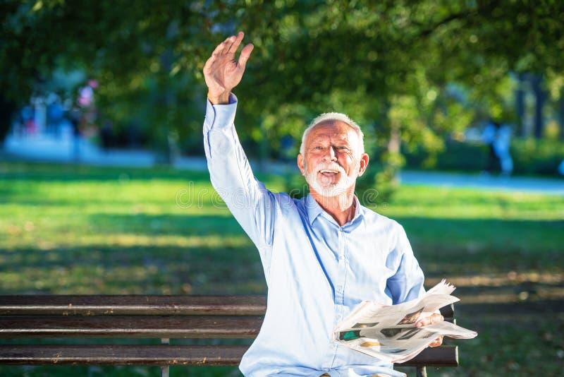 放松在公园在一好日子供以座位在一个长木凳和等待某人的老人 库存图片