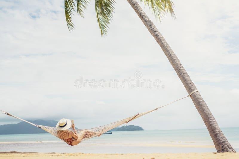 放松在海滩的吊床夏天休假的亚裔妇女 库存照片