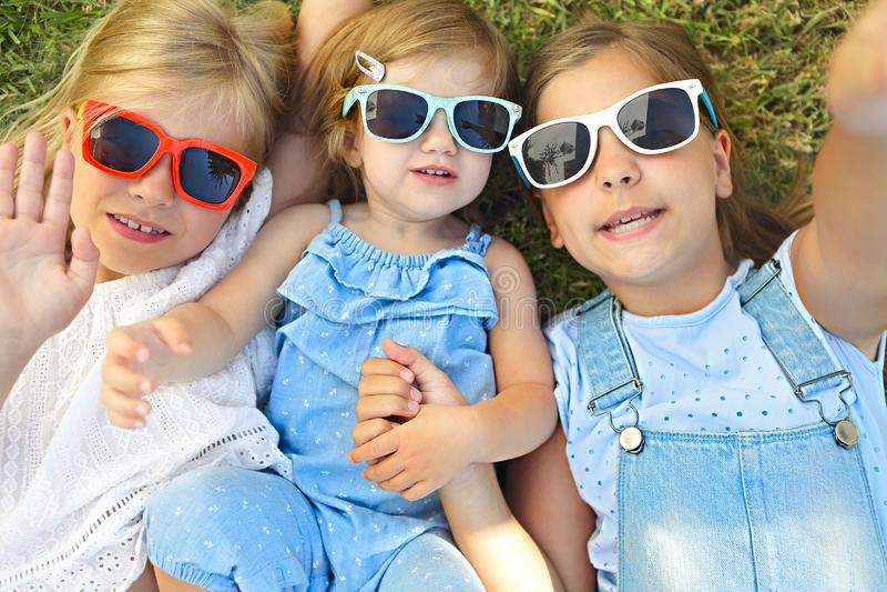 放松在绿草的夏日期间的笑的孩子 库存照片