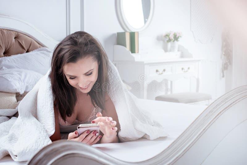 放松和使用智能手机的快乐的妇女 免版税库存图片