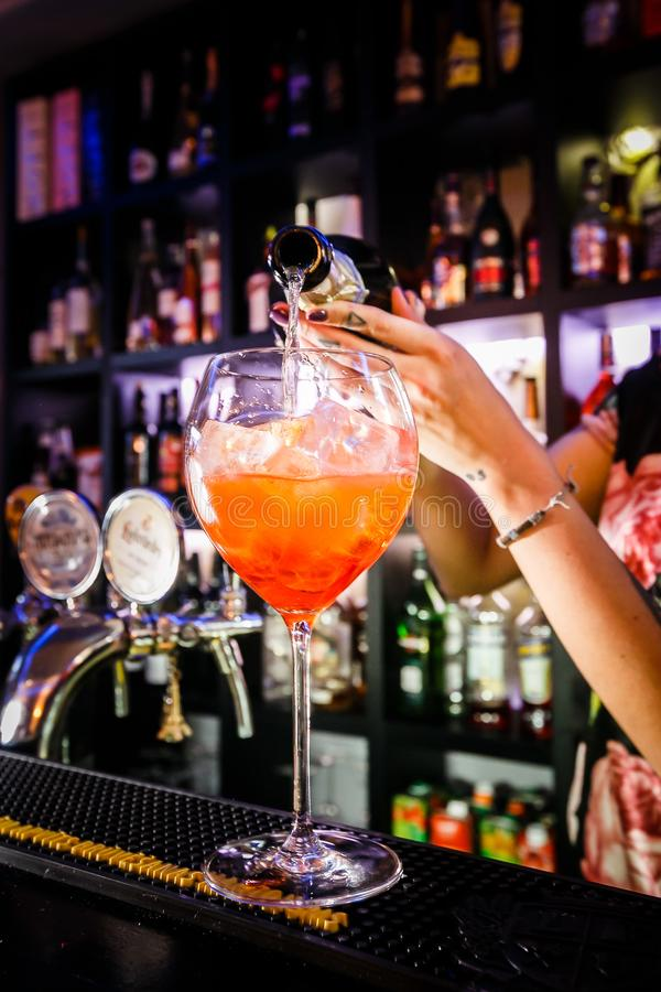 洒酒精的男服务员的手入鸡尾酒杯充满冰 免版税图库摄影