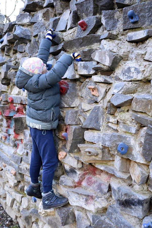 攀登墙壁的年轻男孩 免版税库存照片