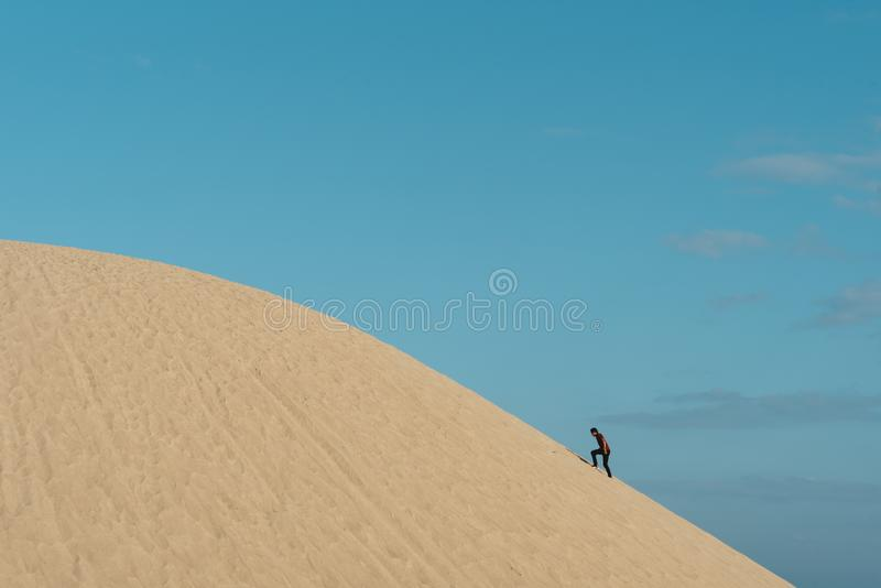 攀登沙丘的年轻成人亚洲男性反对蓝天背景 库存照片