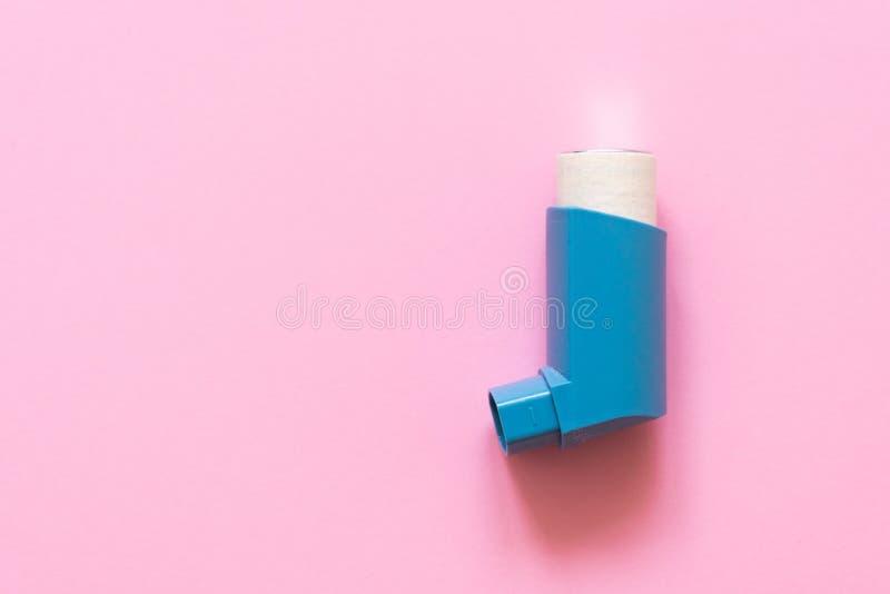 Ærosol för inandning för behandlingen av bronkial astma på en rosa pastellfärgad bakgrund arkivbild