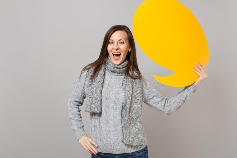 灰色毛线衣的快乐的年轻女人,拿着黄色空的空白的围巾说云彩,在灰色隔绝的讲话泡影 免版税库存图片