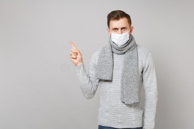灰色毛线衣的,围巾不育的面膜年轻人指向食指的在旁边在灰色墙壁背景 健康 库存照片