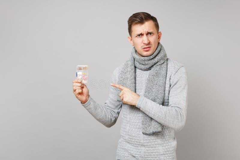 灰色毛线衣的,围巾被憎恶的年轻人指向在每日药片箱子的食指隔绝在灰色背景 健康 免版税库存图片