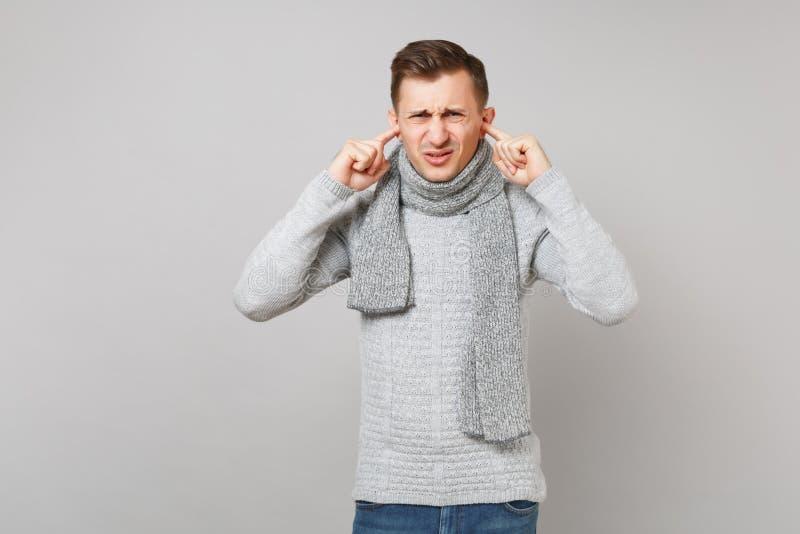 灰色毛线衣的,盖耳朵的围巾被憎恶的年轻人用在灰色墙壁背景隔绝的手指 健康时尚 免版税库存图片