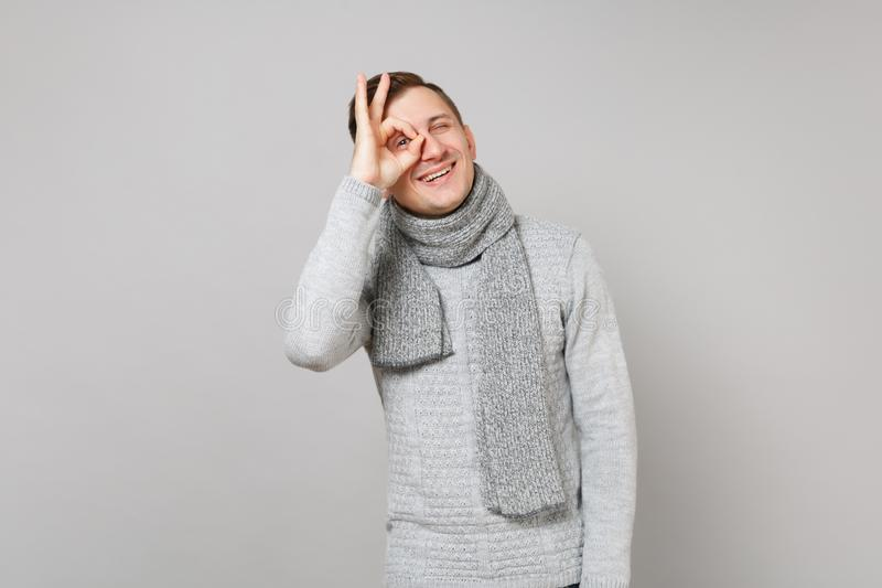 灰色毛线衣,围巾藏品手的快乐的年轻人在眼睛附近,仿效玻璃或双筒望远镜在灰色 图库摄影
