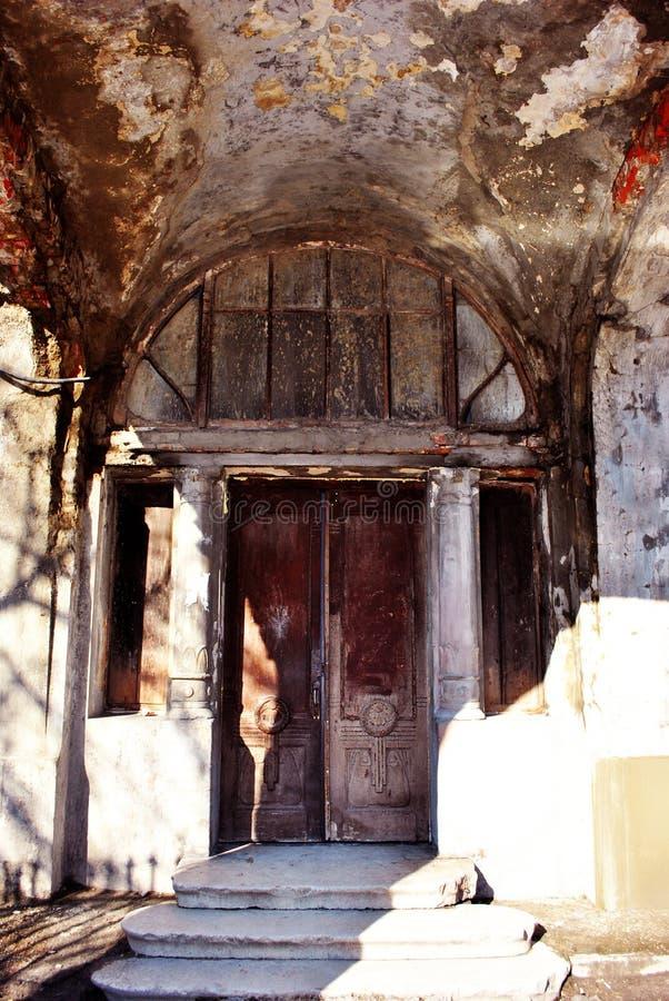 灰色老城堡破坏了墙壁和门与专栏在边,步与明亮的阳光 免版税库存照片