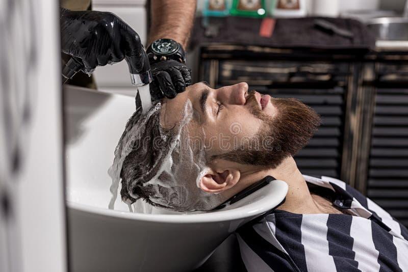 理发师在理发店洗人的头发 免版税库存照片