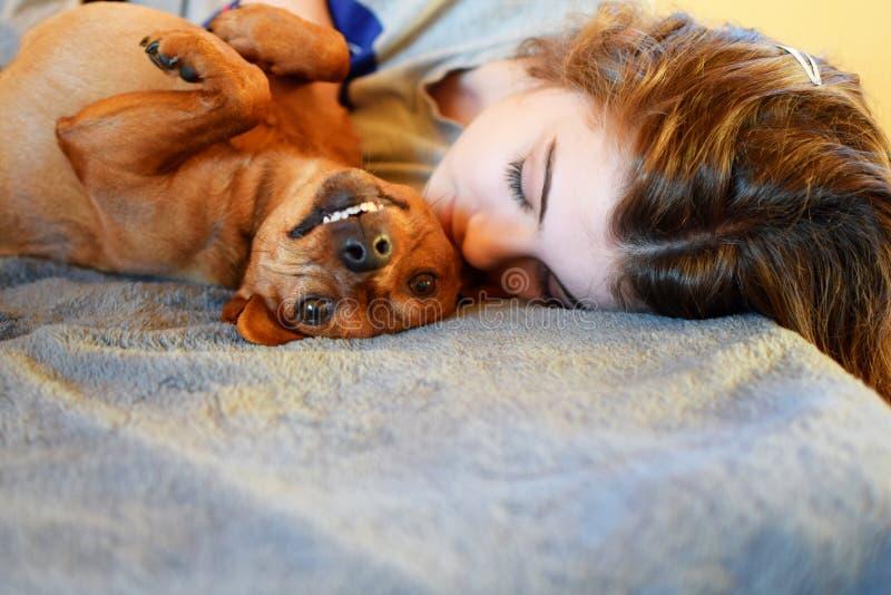 睡觉在床和微笑的狗上的青少年的女孩 库存图片