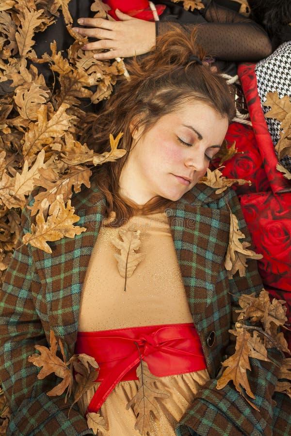 睡觉的妇女在地板充分躺下叶子 森林在秋天 图库摄影