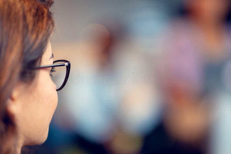 确信地微笑年轻女实业家的戴着眼镜,当站立在有工作在时的同事的一个办公室 库存照片