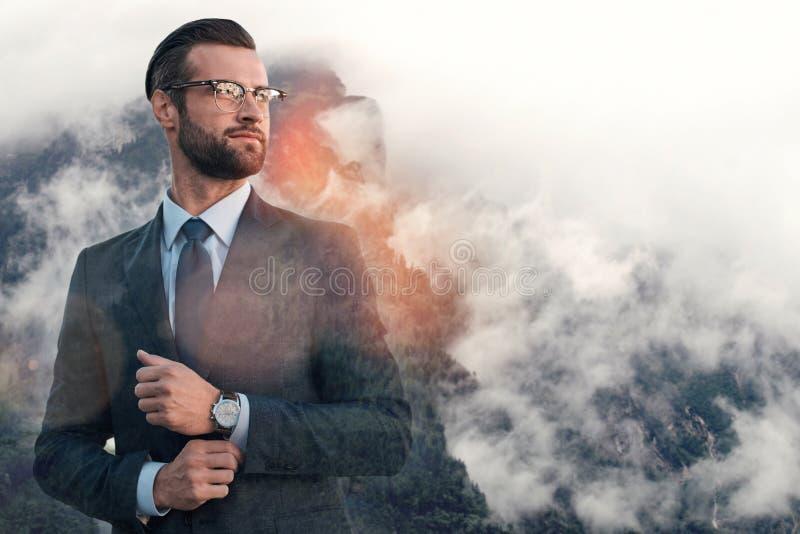 确信的生意人 调整他的袖子的时兴的年轻人,当站立反对有雾的山背景时 库存图片