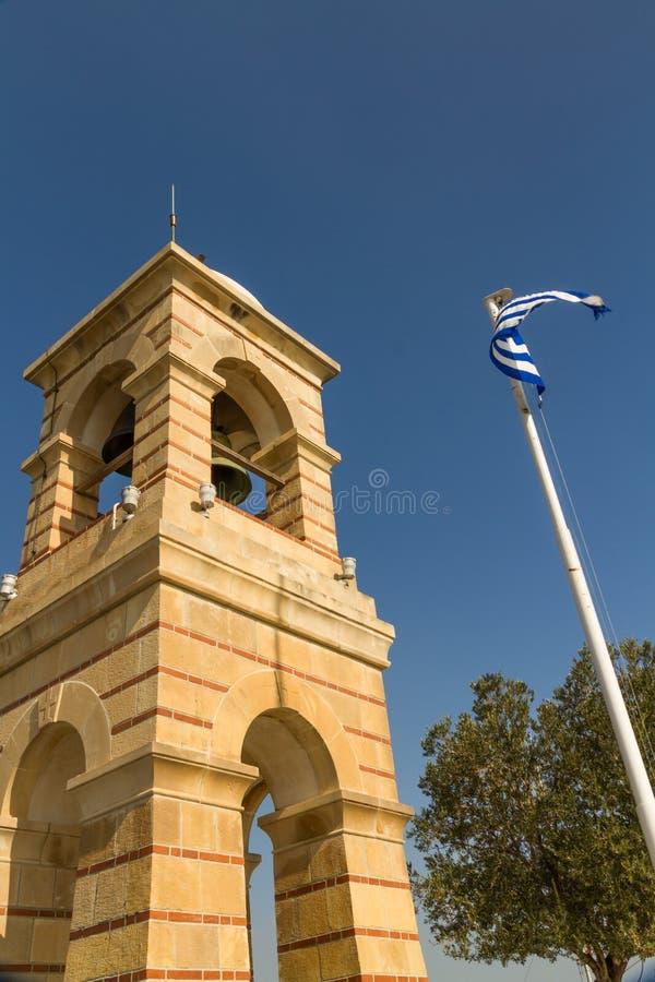 社论,在吕卡维多斯观看的地区的钟楼与希腊旗子 免版税库存照片