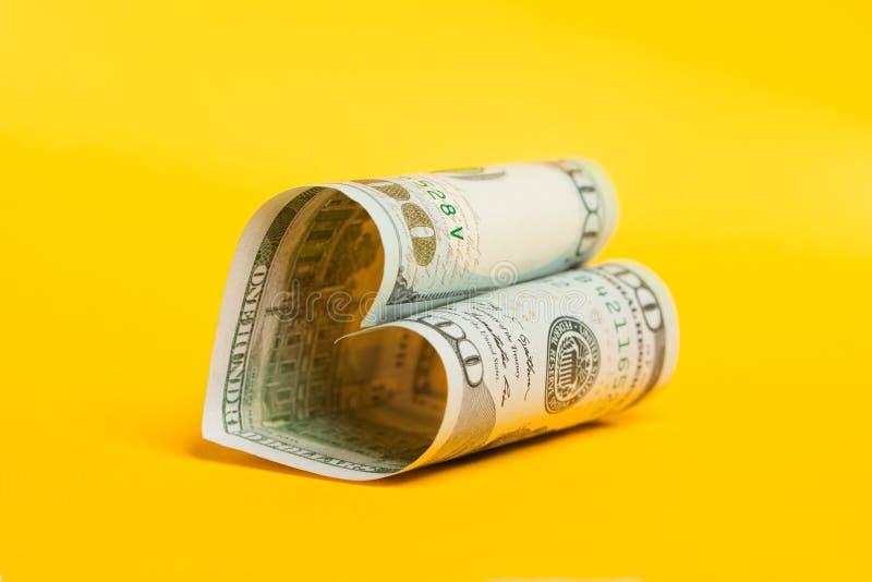 100票据 美元笔记的心脏关于黄色的 双赢,礼物、储蓄兴趣和商业金钱投资赢利概念 库存图片