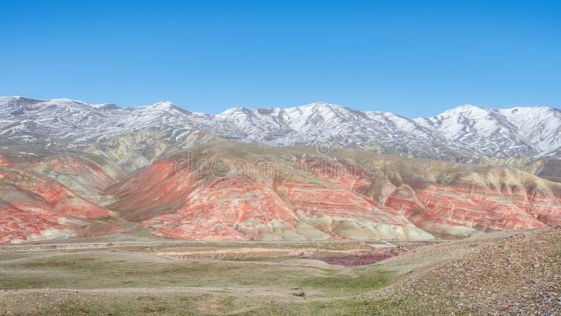 积雪的令人惊讶的镶边红色山在冬天 免版税库存照片