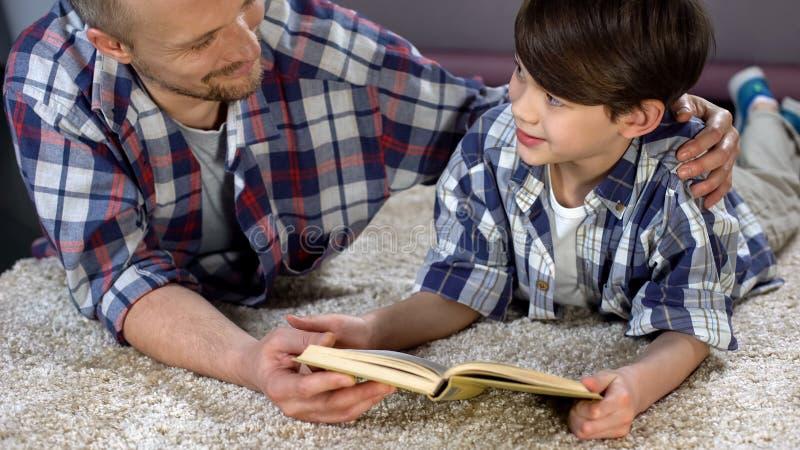 称赞爱恋的父亲听儿子读书,支持和他,家庭作业 库存照片