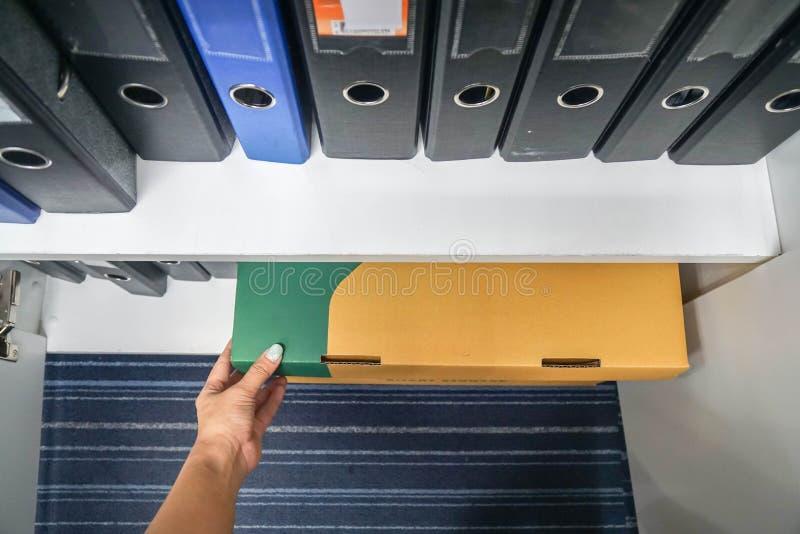 秘书拉扯从办公室内阁的被分类的工商业票据箱子 免版税库存图片