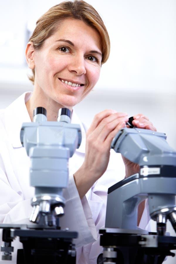 科学家与显微镜一起使用 免版税库存照片