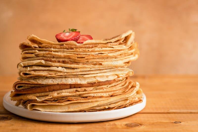 稀薄的薄煎饼、俄式薄煎饼或者绉纱在木背景 免版税库存照片