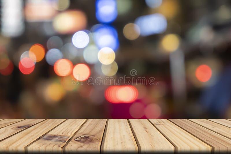 空的木桌在前面抽象被弄脏的bokeh五颜六色的背景中 免版税库存照片
