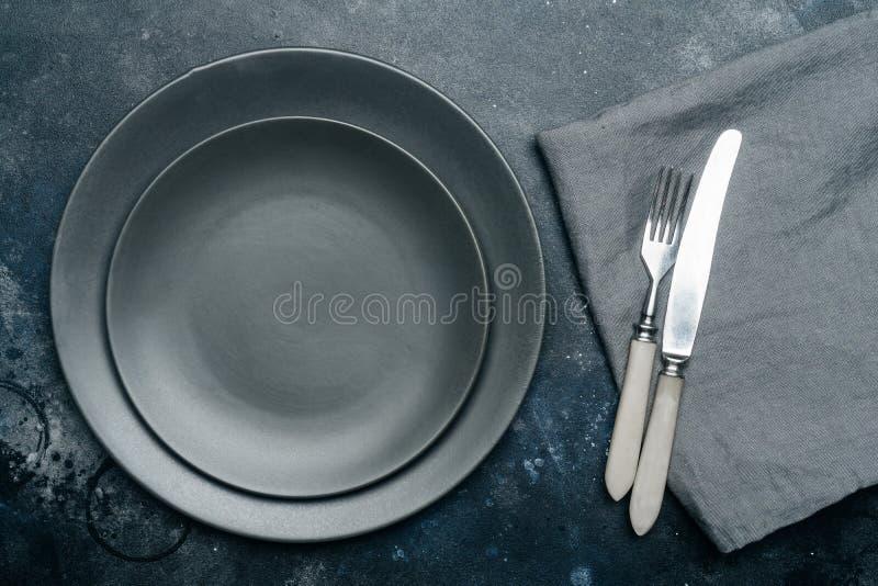 空的灰色板材陶瓷在与刀子和叉子的深灰背景,装饰用淡紫色和餐巾花束  免版税图库摄影