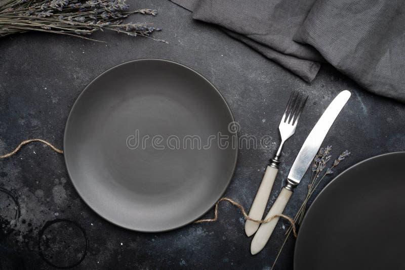 空的灰色板材陶瓷在与刀子和叉子的深灰背景,装饰用淡紫色和餐巾花束  库存照片
