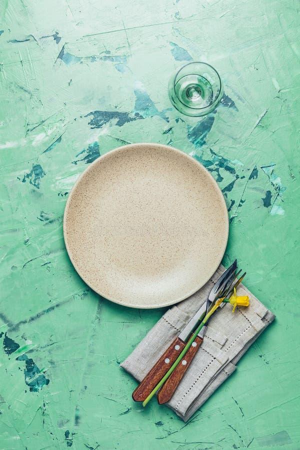 空的米黄板材和利器有黄水仙的在餐巾 免版税库存照片