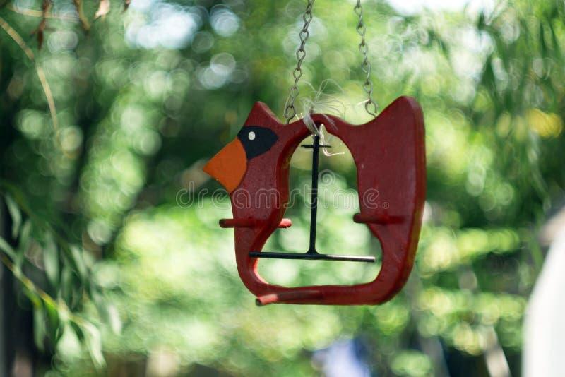空的红色鸟饲养者在后院有梦想的bokeh背景 库存照片