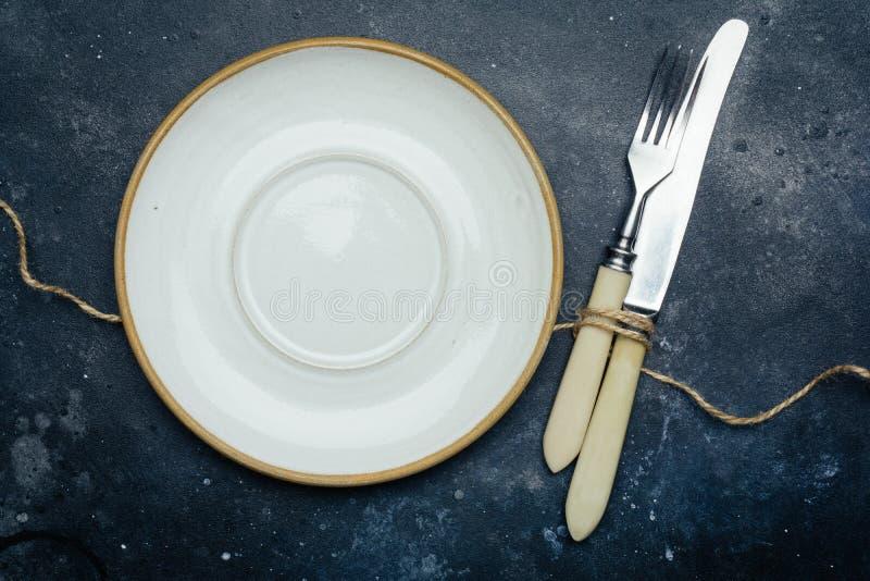 空的白色板材陶瓷,土气在与刀子和叉子的深蓝背景 图库摄影