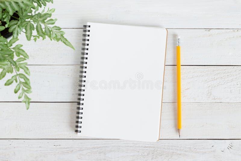 空白的在白色木头,笔记本平的被放置的照片的笔记本与和铅笔您的消息的 免版税库存图片