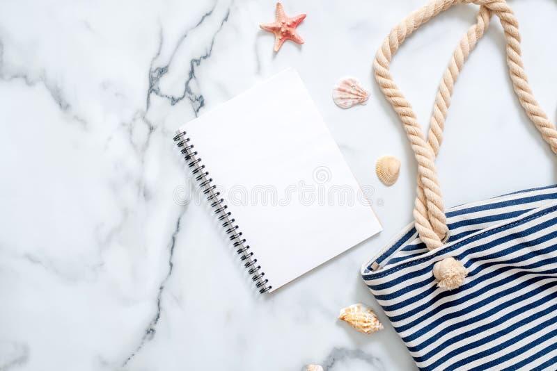 空白的笔记薄,镶边夏天袋子,在大理石背景的贝壳 旅行家,秀丽博客作者,数字游牧人,臀部妇女的书桌  免版税库存照片
