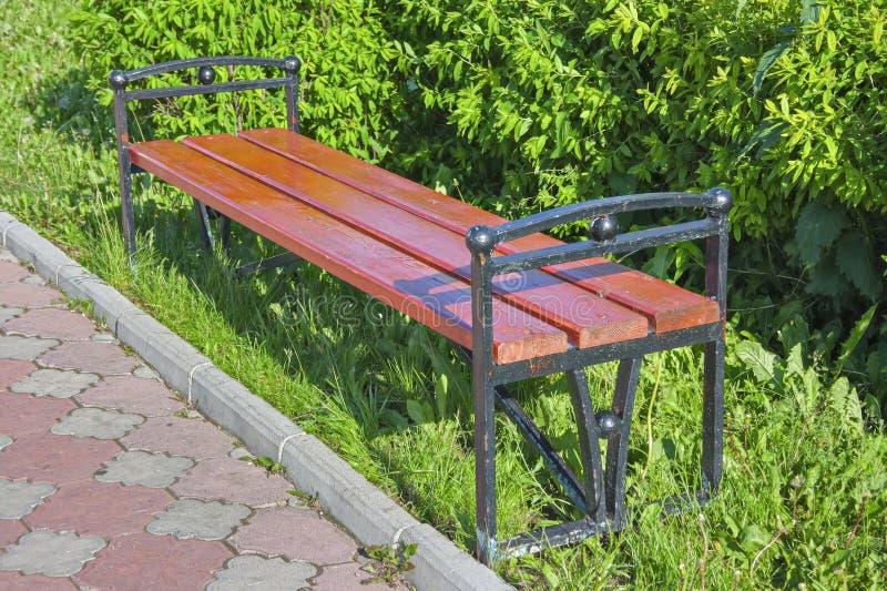 空白的老长木凳在庭院或公园的一个遮荫区域 库存图片