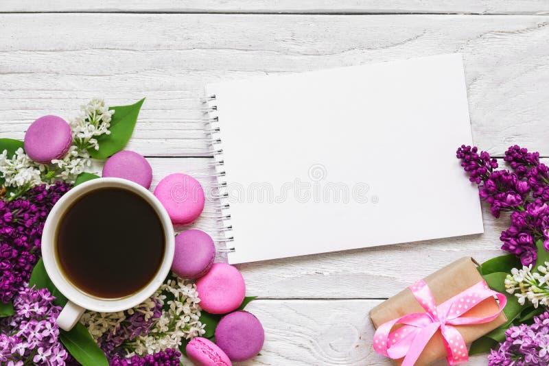 空白的贺卡或婚姻的邀请与淡紫色花、咖啡杯、蛋白杏仁饼干和礼物盒 库存图片