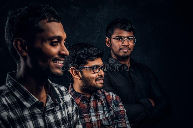 穿便服的三名愉快的印度学生特写镜头画象对黑暗的墙壁 免版税图库摄影