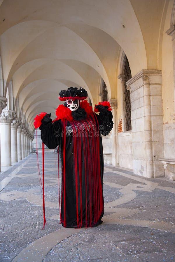 穿威尼斯面具和黑色和红色服装的人在共和国总督的宫殿下曲拱在威尼斯狂欢节在威尼斯意大利 库存图片