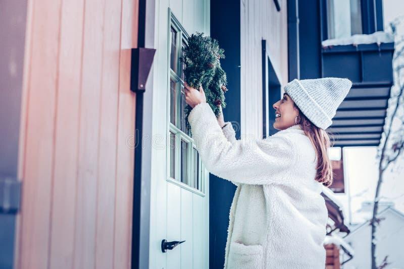 穿温暖的米黄外套的妇女装饰房子前面  免版税图库摄影
