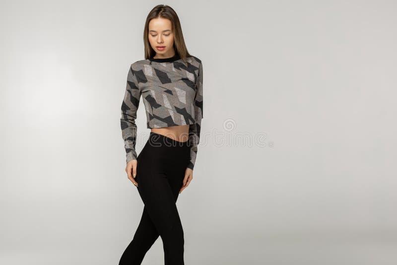 穿时髦黑体育衣裳的华美的年轻女人播种的射击 免版税图库摄影
