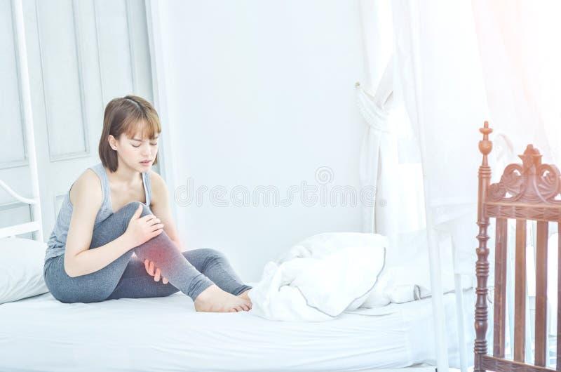 穿灰色睡衣的妇女坐长沙发使用把柄对脚 免版税图库摄影