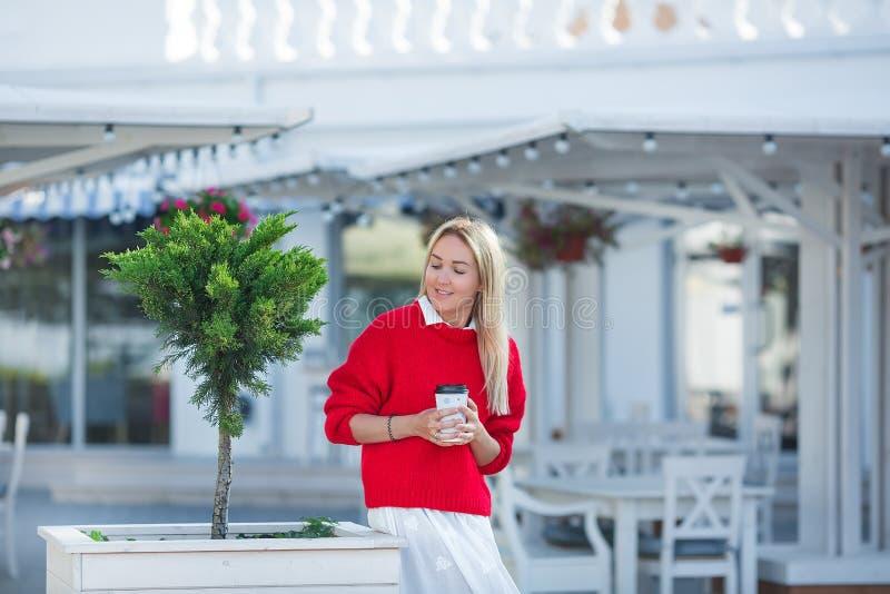 穿着红色毛线衣和白色裙子的壮观的白种人女孩夫人特写镜头画象  讨人喜欢的长发白肤金发的妇女 图库摄影