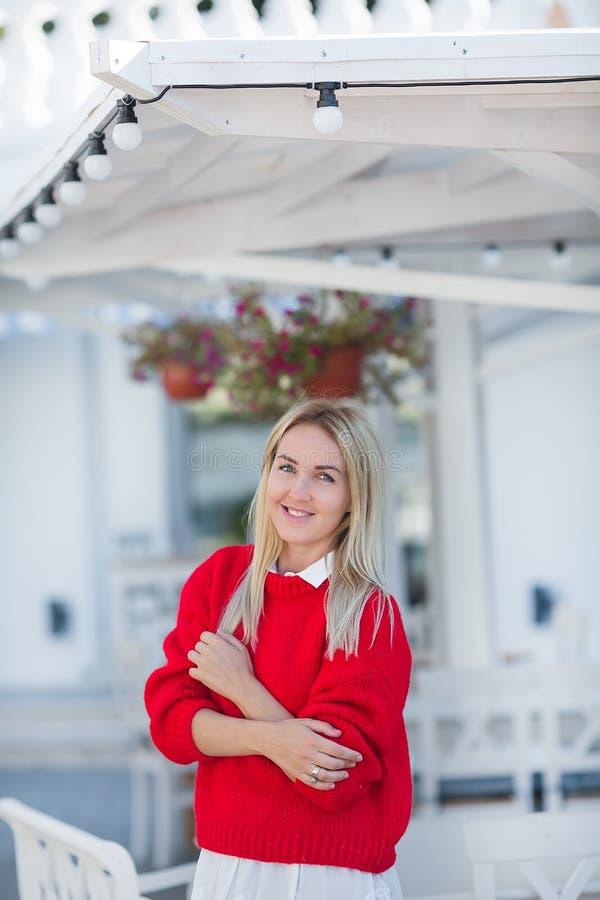 穿着红色毛线衣和白色裙子的壮观的白种人女孩夫人特写镜头画象  讨人喜欢的长发白肤金发的妇女 免版税库存图片