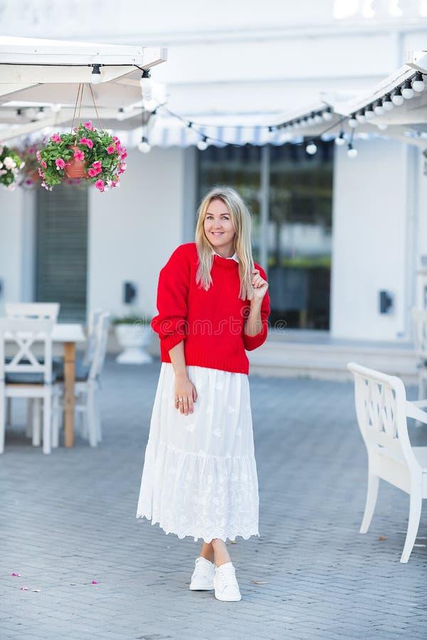 穿着红色毛线衣和白色裙子的壮观的白种人女孩夫人特写镜头画象  讨人喜欢的长发白肤金发的妇女 免版税库存照片