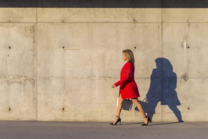 穿红色夹克,裙子和拿着一个白色提包的一名端庄的妇女的侧视图,当走在街道在一好日子时 免版税库存照片